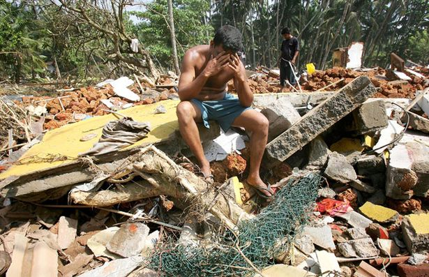 A Sri Lankan man despairs as he searches among the ruins of his house devastated by the Boxing Day Tsunami, 2004.