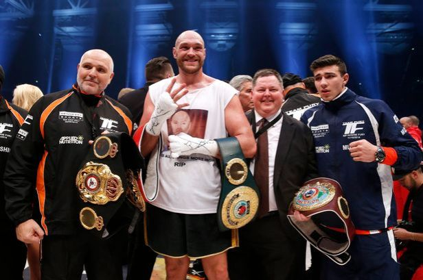 Peter Fury (left) standing next to his nephew Tyson Fury (centre) on 28 Nov 2015 after beating Wladimir Klitschko to win the world heavyweight title